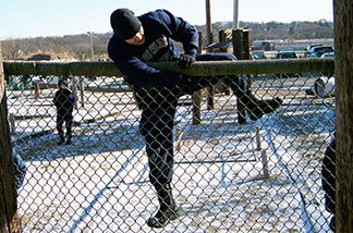 police recruit climbing a fence
